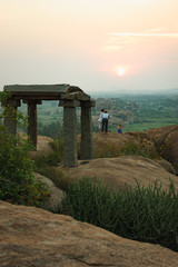 Fototapete - Picturesque view from the Malyavanta Hill at sunset overcast sky in Hampi, Karnataka, India. Tourists enjoy and photograph the sunset