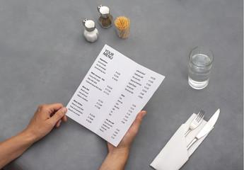 Hands Holding Menu at Diner Table Mockup