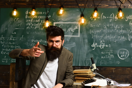 Confident teacher sit at desk. Businessman with beard in suit. Bearded man with typewriter, books and microscope. Scientist in eyeglasses with chalkboard on background. Science and research