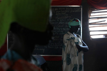 An internally displaced woman prays inside a church in the UNMISS Protection of Civilian 3 site outside Juba