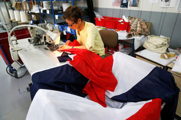 A worker sews French flags at Faber France factory, to meet fans' demand several days before the Soccer World Cup Final where France plays Croatia, in Wavrin