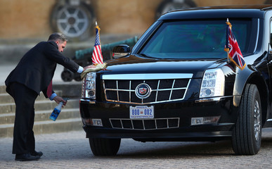 A member of the U.S. President's staff cleans the front of the presidential limousine at Blenheim Palace, where the U.S. President is attending a dinner with British Prime Minister Theresa May, near Oxford