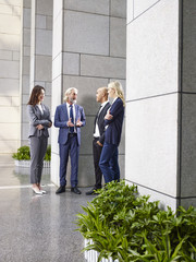 multi-ethnic corporate executives standing talking in lobby of modern office building