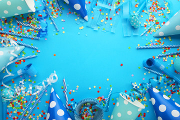Birthday party caps, blowers and paper straws on blue background
