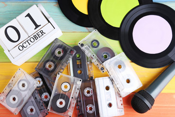 Vinyl records with cassette tapes, microphone and calendar cubes on wooden table