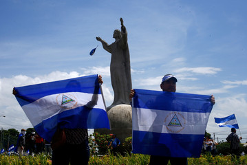 """Demonstrators hold up national flags during a march called """"Together we are a volcano"""" against Nicaragua's President Daniel Ortega's government, in Managua"""