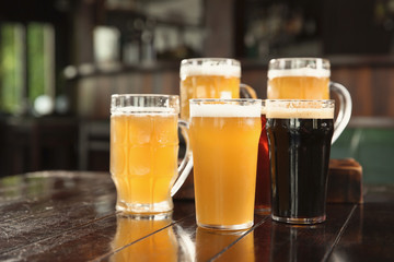 Glasses of tasty beer on wooden table in bar