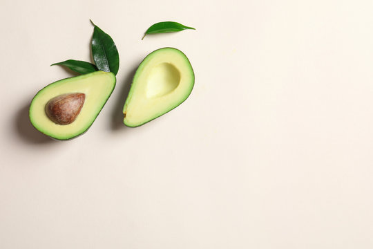 Ripe sliced avocado on light background