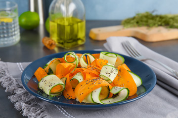Plate with tasty carrot salad on table