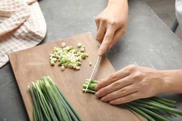 Woman cutting fresh green onion on wooden board