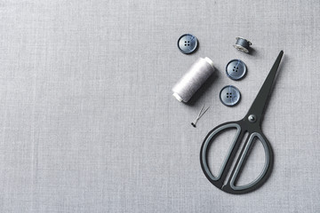 Set of tailoring accessories on grey fabric, top view