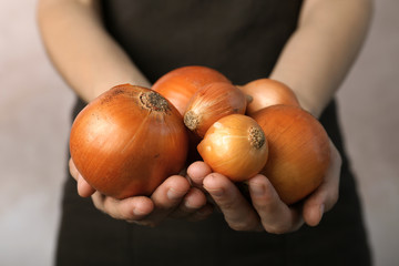 Woman holding ripe onions on grey background
