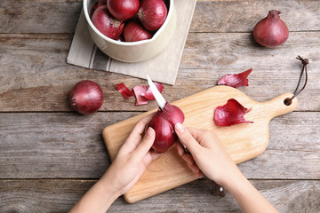 Woman peeling ripe red onion on wooden table, top view