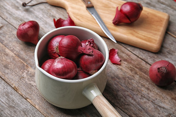 Saucepan with ripe red onions on wooden table