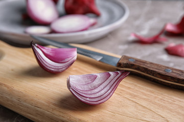 Wooden board with sliced ripe red onion, closeup