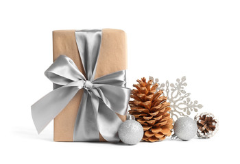 Beautifully wrapped gift box, pine cones and decorations on white background