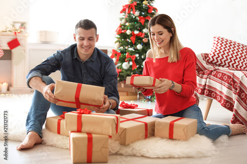 young couple with christmas gifts at home