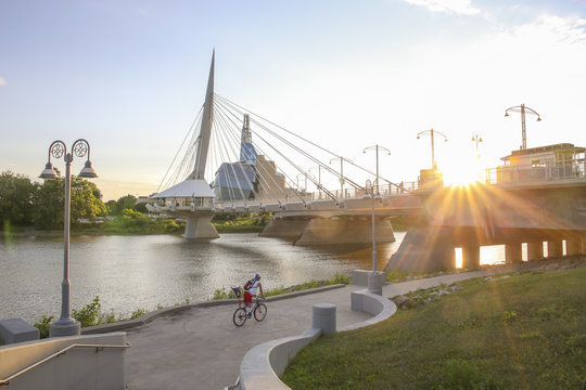 Cyclists along Red River in a sunny day. Peaceful sunset scene. Winnipeg, Canada.