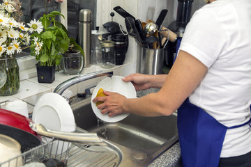 Woman washes dishes in the kitchen