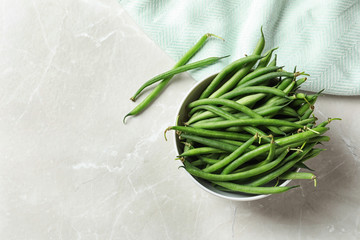 Bowl with fresh green French beans on table, top view