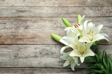Flat lay composition with beautiful blooming lily flowers on wooden background