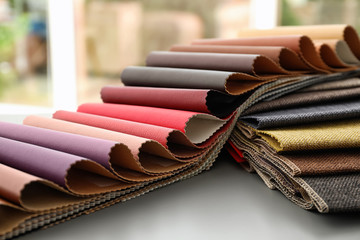 Fabric and leather samples of different colors for interior design on table