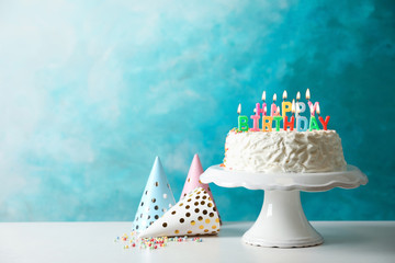 Birthday cake with candles on table against color background