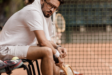 serious tennis player sitting on chair with tennis racket at court and looking at camera