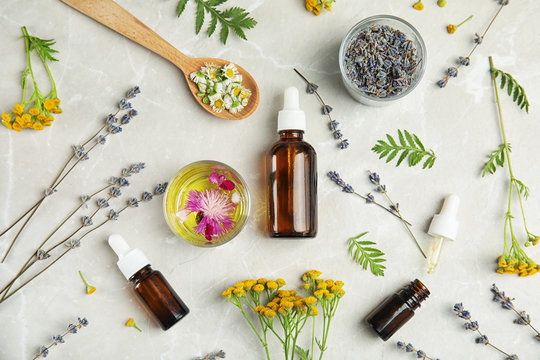 Flat lay composition with essential oils and flowers on light background