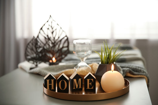 Tray with burning candle, word HOME and hourglass on table indoors