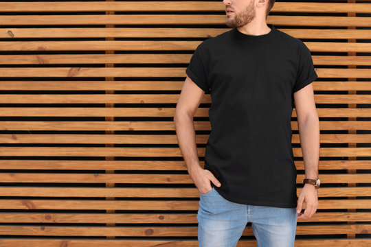 Young man wearing black t-shirt against wooden wall on street. Urban style