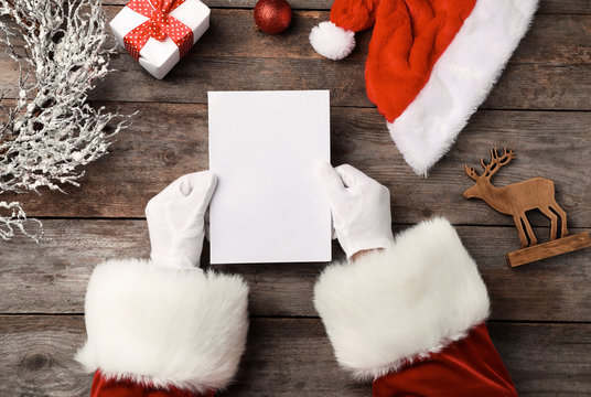 Santa Claus reading letter from child at table, top view. Christmas celebration