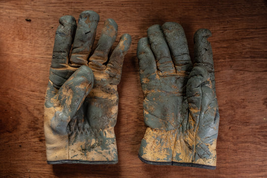 old battered and worn work gloves on wooden board