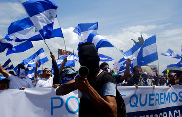 "A demonstrator holds a homemade mortar during a march called ""Together we are a volcano"" against Nicaragua's President Daniel Ortega's government, in Managua"