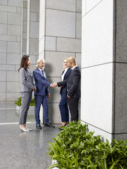 multi-ethnic corporate executives shaking hands in lobby of modern office building