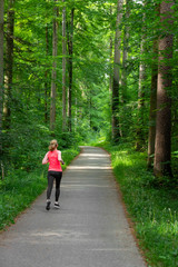 Young woman running along path through green forest.