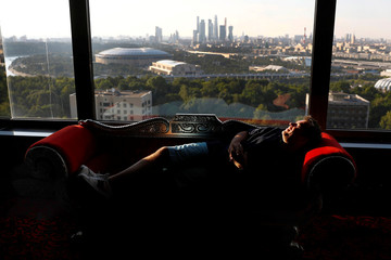 Reuters photographer Carl Recine relaxes on a sofa on the top floor of the hotel Korston with the Luzhniki stadium in the background in Moscow