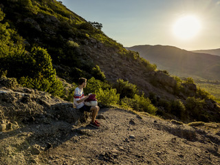 portrait of man sitting on the mountain with backpack in casual clothes during beautiful sunset