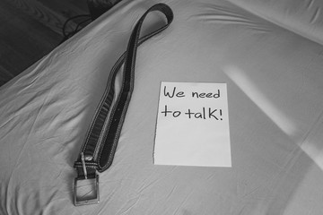 a note from infuriated father. leather belt on the bed prepared for spanking. domestic discipline. talking with strict parents about behaviour