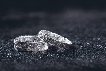 Two wedding rings on dark background with copy space.