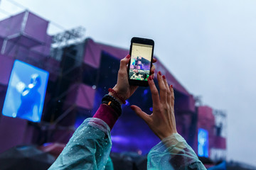 The girl takes a music festival, a concert on the smartphone. Rainy weather, drops on the screen