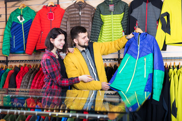 Couple examining windcheaters in store
