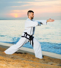 Man in uniform doing taekwondo exercises at  sunset sea shore