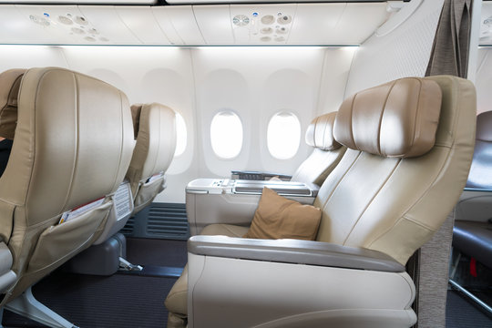 Empty leather seats in row atBusiness class reclined seats of airplane..