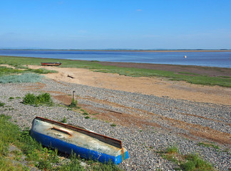 view of the ribble estuary in lancashire with a small fishing boat on the river and and old derelict rowing boat on the shore with grass covered sand and bright blue summer sky