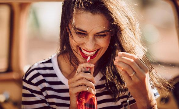 Beautiful young woman drinking soda