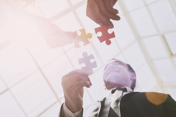 Three Smart Business Partners with Jigsaw Puzzles.