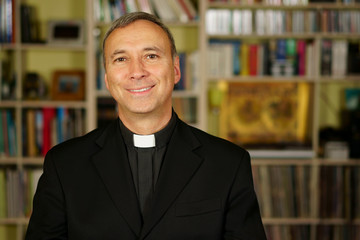 A good looking catholic priest is studying into his library. He looks at us with serenity, peace and optimism.