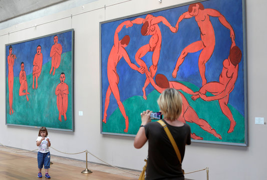 A visitor takes pictures beside painting of the French artist Henri Matisse's 'The Dance' at the Palace square in front of the State Hermitage Museum in St. Petersburg