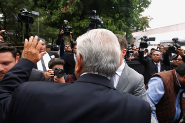 Mexico's President-elect Andres Manuel Lopez Obrador waves to the media as he arrives to a meeting with all the state governors in Mexico City